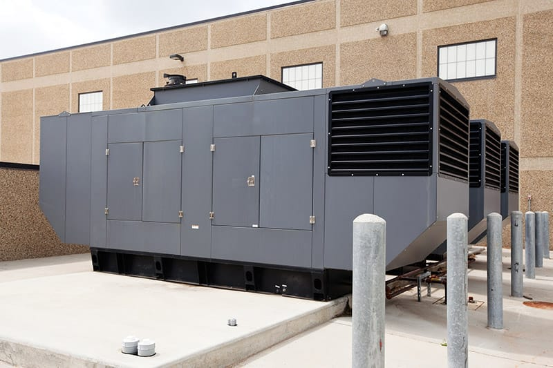 Three large industrial emergency power standby generators. This configuration could power a large facility such as a hospital, school even a small city. The concrete pad in the left foreground is space for an additional generator.